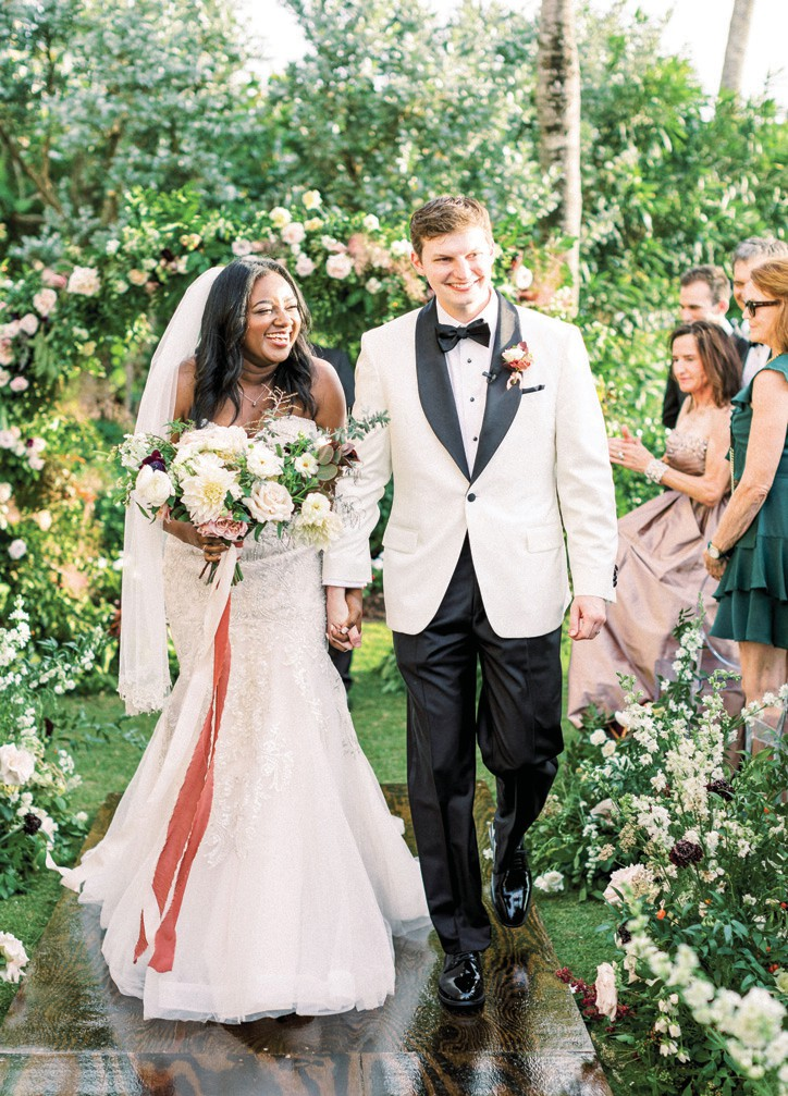 """Right: Charnele and Joe Dernback say """"I do,"""" surrounded by floral installations created by Kaleidoscope Floral."""